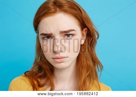 Headshot Portrait of tender redhead teenage girl with serious expression looking at camera. Caucasian woman model with ginger hair posing indoors.Pastel blue background. Copy Space.