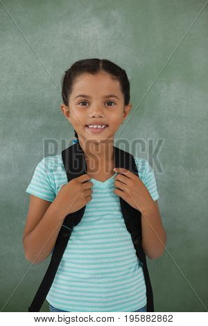 Portrait of young girl with bagpack against chalk board