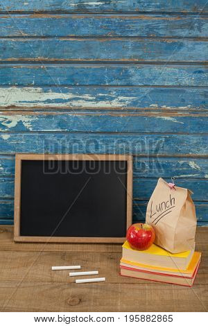 Slate, chalk, apple, lunch bag and books against blue wooden background