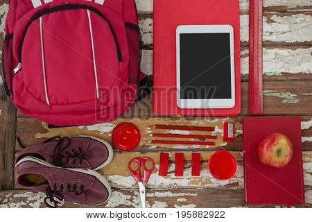 Bagpack, shoes, digital tablet, apple and stationary on wooden background