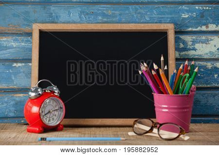 Slate, alarm clock, penholder, pencil and spectacle against blue wooden background
