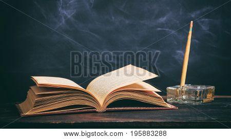 Vintage Book And Ink Pen On Blackboard Background