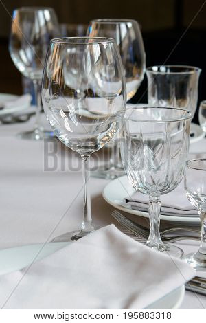 Empty glasses for wine on the holiday table. Serving a formal dining event. Cutlery for people in the restaurant.
