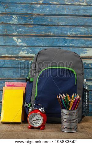 Bagpack, books, alarm clock and pen holder against blue wooden background