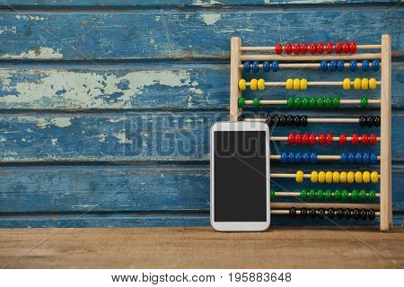 Abbacus game and smartphone against blue wooden background
