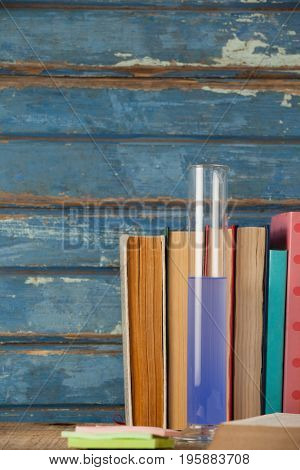 Stack of books, chemical test tube and sticky notes against blue wooden background