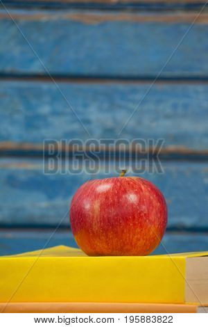 Close-up of stack of books and apple against blue wooden background