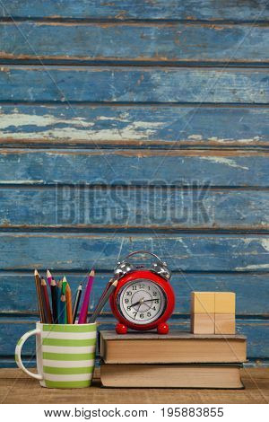 Alarm clock, books, paperweight and pen holder against blue wooden background