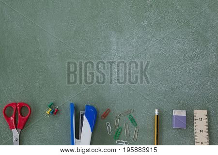 Overhead view of various school supplies arranged on chalkboard