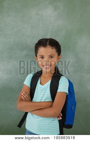 Portrait of cute school girl standing with arms crossed against chalkboard