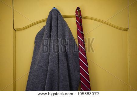 Close-up of school uniform hanging on yellow door