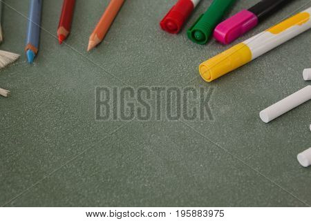 Close-up of various color pencils, marker pens and chalk on chalkboard