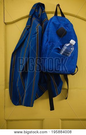 Close-up of school uniform and bag hanging on yellow door