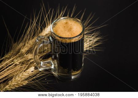 Wheat spikelets with one mug of beer on empty black background. Ripe ears of wheat barley with beer glass.