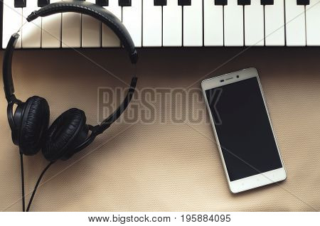 The headphones are on the synthesizer. The synthesizer stands on a beige background. Nearby is the phone. View from above.