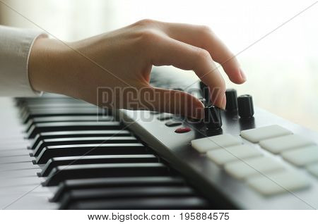 The woman tunes the synthesizer. Dressed in a white shirt side view. In the frame one hand