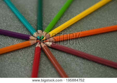 Close-up of various color pencils arranged on chalkboard