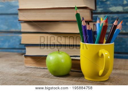 Book stack, color pencils and apple arranged on wooden table