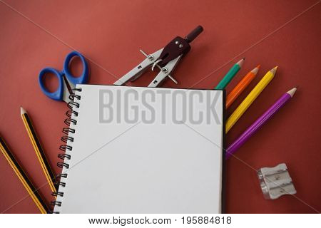 Close-up of various school supplies arranged on red background