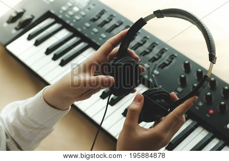 A woman in a white shirt is holding headphones in front of a synthesizer. There are two hands in the frame