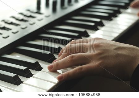 A woman is playing a synthesizer. In the frame one hand side view