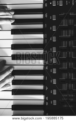 Female hands are playing a synthesizer. Black and white photo. View from above. Vertical photo