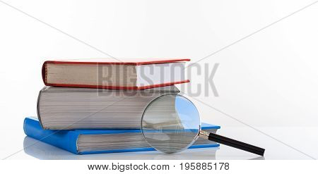 Books Stack And Magnifying Glass On White Background