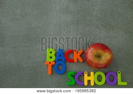 Close-up of block letters and apple arranged on chalkboard