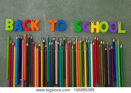 Close-up of block letters and color pencils arranged on chalkboard