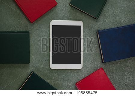 Overhead view digital tablet surrounded with colorful organizers on chalkboard