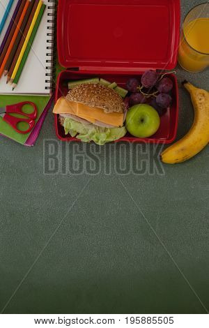 Overhead view of school supplies and lunch box arranged on chalkboard