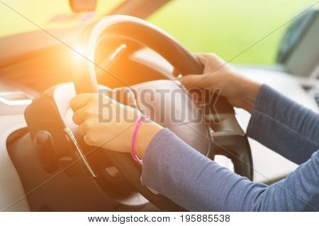 Woman's hands holding steering wheel