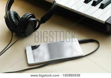 Headphones connected to the phone lying next to synthesizer on a light background. Side view