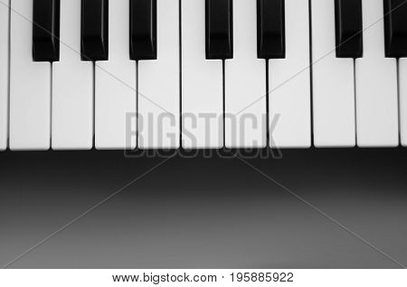 Keyboard synthesizer on a gray background. Black and white photo. View from above