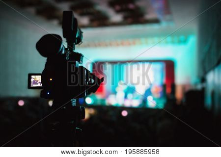 Video camera at the concert. Capture a video. Blue light in the hall. Creative work. To shoot a movie. Silhouette of a video camera. To shoot a video at a concert on the camera. A large video camera on the tip. Video reportage