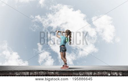 Cute young girl standing on house roof and looking in spyglass