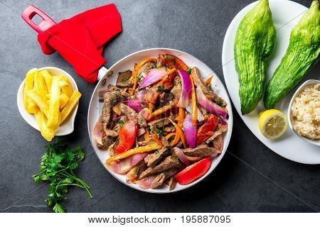 Peruvian Dish Lomo Saltado - Beef Tenderloin With Purple Onion, Yellow Chili, Tomatoes In Pan. Tot V