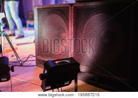 Large music speakers. Color lighting in the concert stage. Soffits illuminate the scene. Electric light. Equipment on stage for a concert. Powerful music speakers. Big speakers at a rock concert. Loud speakers at the festival