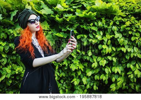 Red-haired stylish girl with a turban on her head and sunglasses with a mobile phone on a background of green foliage. Do selfie on your mobile phone. Dial a number on mobile device. Fashionable device. New device in female hands. Do selfie on a backgroun