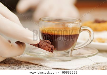 Close up of hot coffee with a chocolate cake in a blurred background.