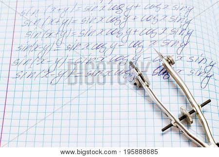 Compasses on abstract in algebra for drawing on a notebook sheet with mathematical calculations section of trigonometry