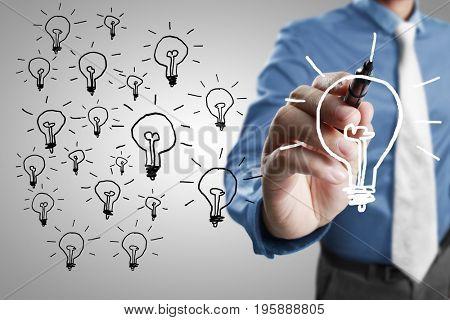 Businessman drawing light bulb on whiteboard