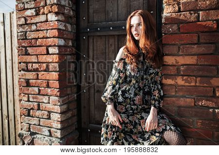 Stylish red-haired girl in a dress and pantyhose in a grid posing outside. Fashion Photo. Beautiful fashion young girl. Sexy fashion young woman. Attractive fashion thin model. Stylish fashionable dress on girl. Fashion concept