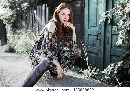 Stylish red-haired girl in a dress and pantyhose in a grid posing outside. Fashion Photo. Beautiful modern young woman. Sexy stylish modern model. Attractive modern girl. Stylish modern fashionable dress on woman. Fashion concept