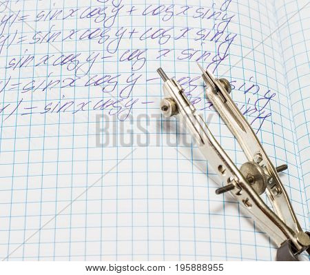 Tool for drawing lies on an open notebook for mathematics is a metal compasses