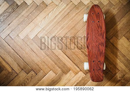 New brown skateboard on a wooden background. Board for skateboard on the floor. Skateboard on a wooden background. Loving a hobby skateboard.