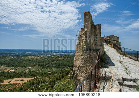 Panoramic view of the castle of Baux-de-Provence at the top of the hill, with the fields and hills of Provence just below. Bouches-du-Rhône department, Provence region, southeastern France