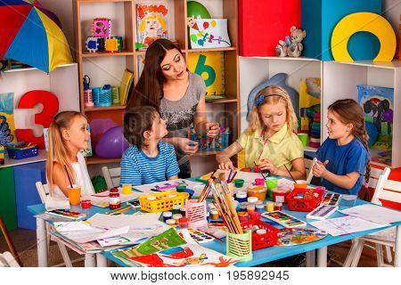 Small students with teacher finger painting in art school class. Mom and kids at home. Children with teacher preparing exhibition of children's drawings. Favorite children's teacher.