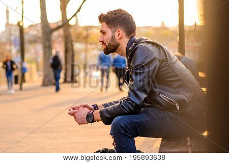 A handsome young hipster man sitting on a bench in the sunset and using his smartphone