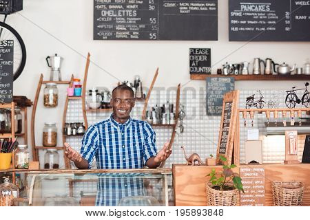 Portrait of a friendly young African entrepreneur smiling while standing welcomingly behind the order counter of his trendy cafe